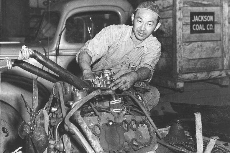 Man works on the mechanics of an engine