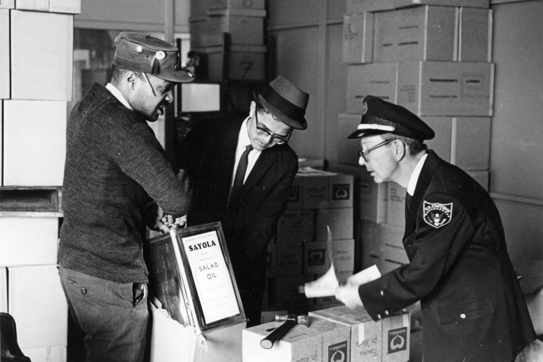 Two young men hold up large containers of cooking oil for a U.S. Customs agent to inspect.