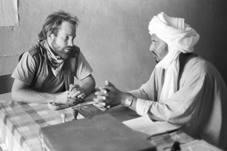 Two men sitting across the table from one another, talking.