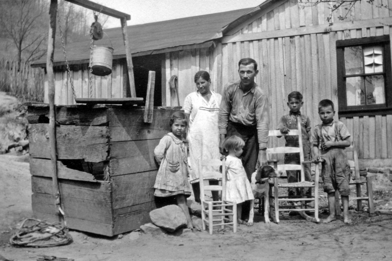 A family of 6 and a dog stand next to a well outside a house, with three wooden chairs