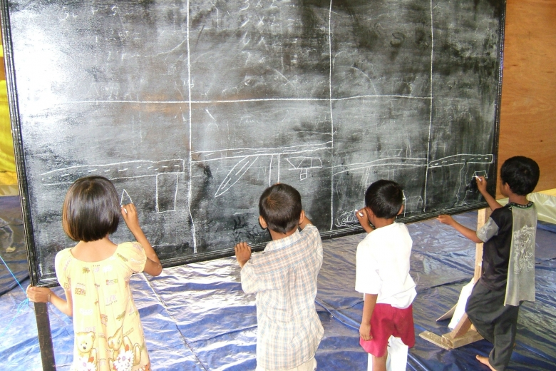Group of four children draw on a blackboard with chalk.