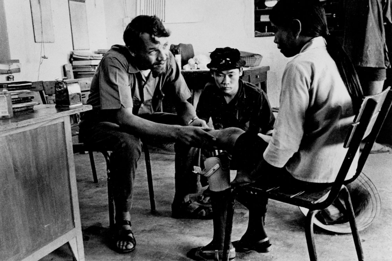 Young man speaks to a woman sitting in a chair with a prosthetic leg while another young man looks on.