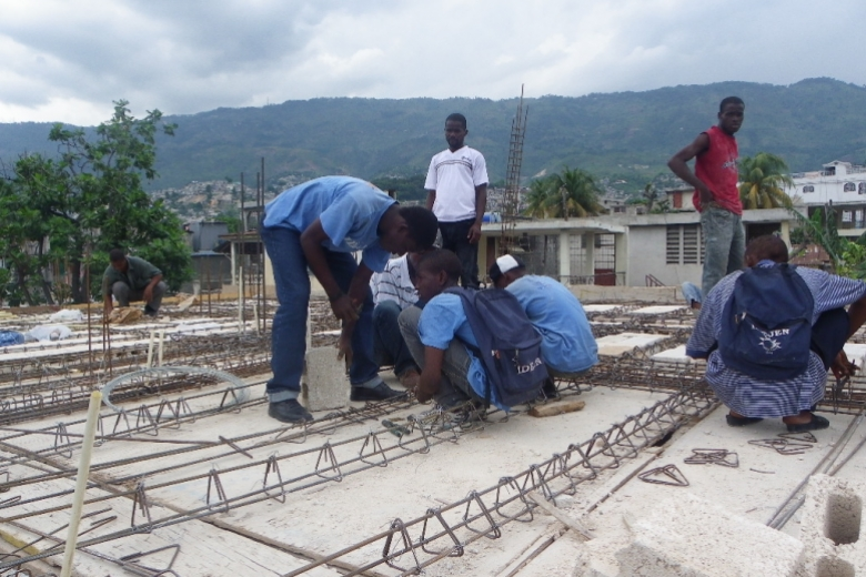 Young adults work on a construction project with rebar.
