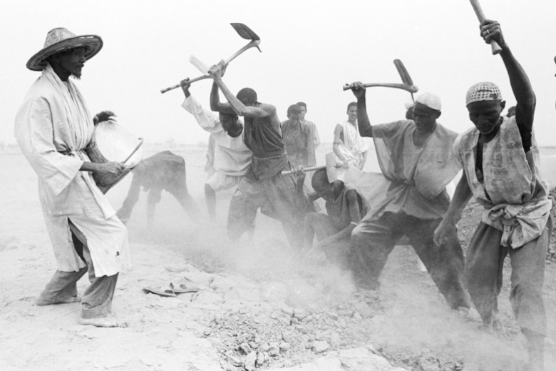 One man plays a drum, facing other men as they plow the soil using hand tools. Photo: Terry Foss