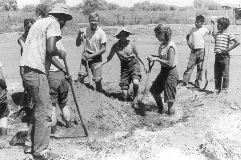 A group of people digs in clay soil