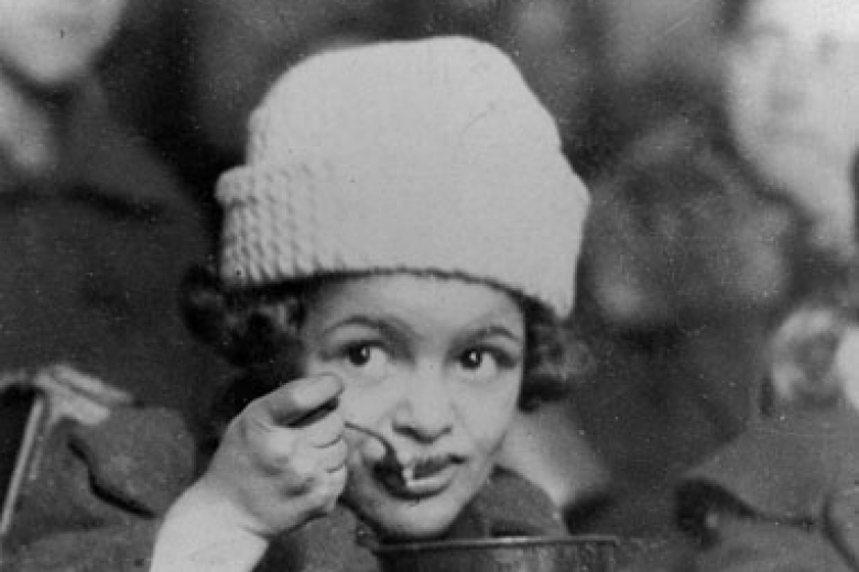 Child wearing a hat, eating out of a metal bowl with a spoon and bread nearby
