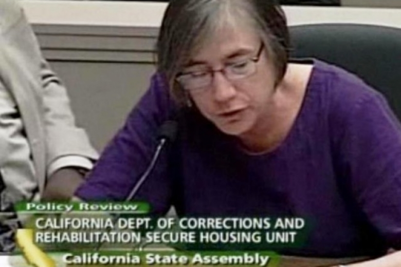 Woman reads talking points at a California State Assembly hearing.