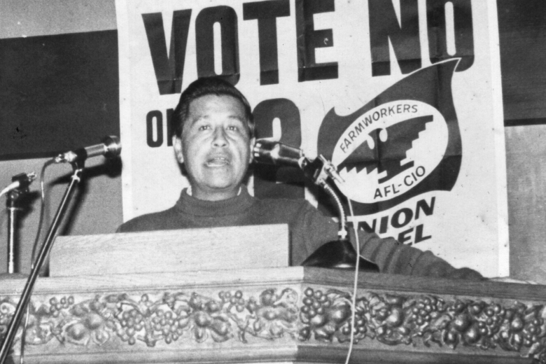 Man speaks at a podium in front of two microphones, with a farm workers union banner behind him.