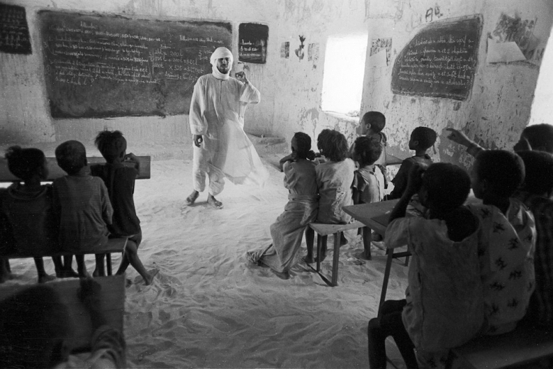 Man speaks to classroom full of children, standing in front of a blackboard. Photo: Terry Foss