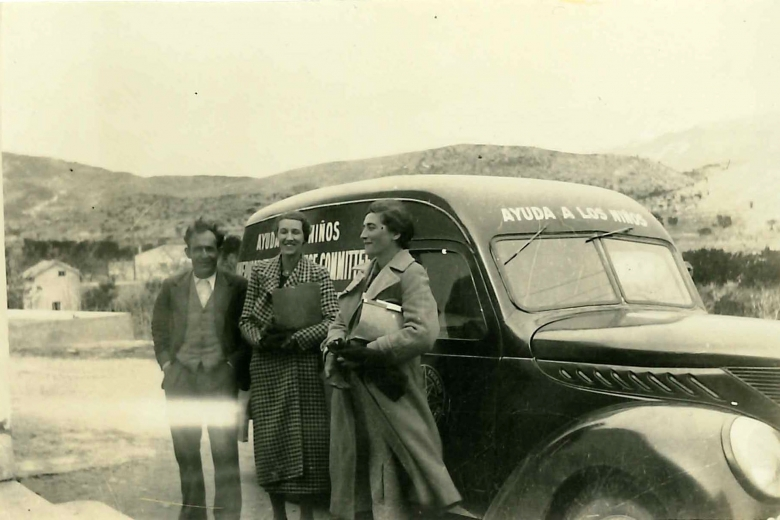 Two women holding files standing in front of a vehicle.