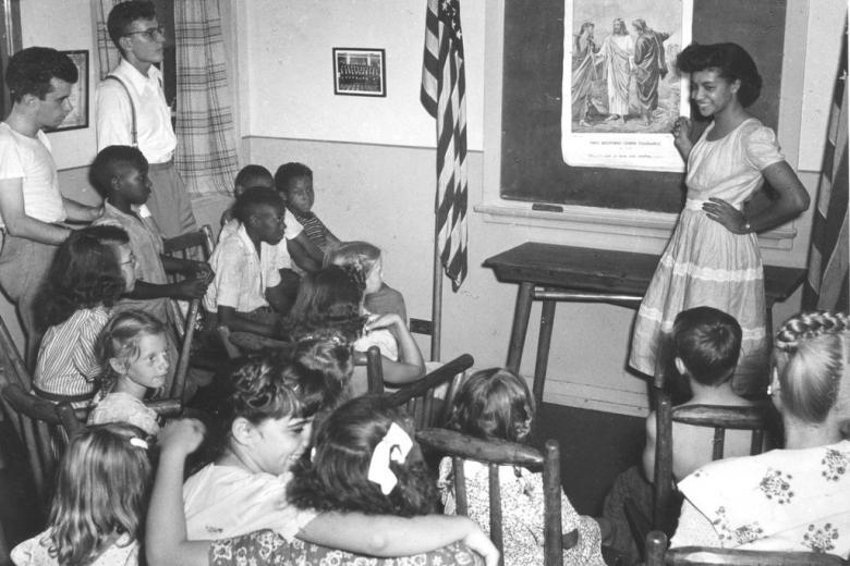 African American woman teaches classroom of children.