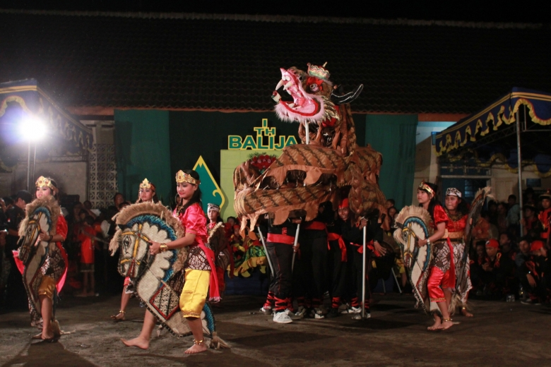 Group of people wearing colorful clothes enact a dramatic scene with puppets of horses and dragons.