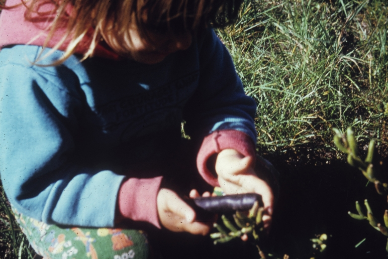 Child squats in the grass holding a small, brown cylinder.