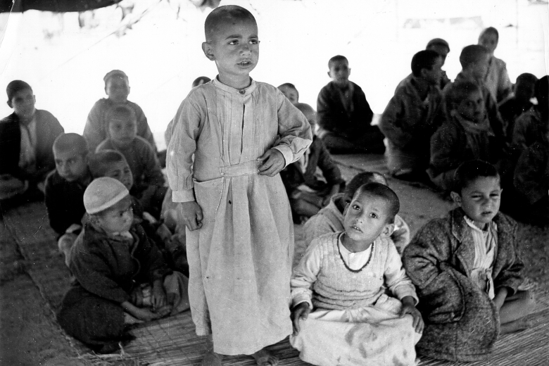 Young boy standing while other children sit on the ground nearby.