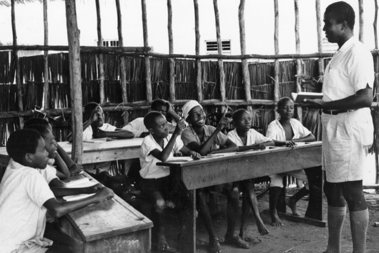 Young man teaches nine children in an open-air classroom.