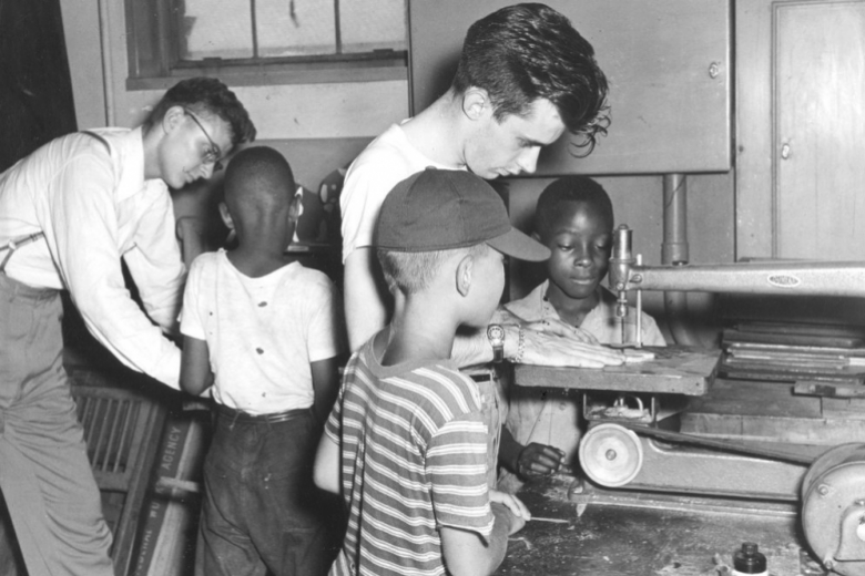 Two young men teach boys in machine shop.