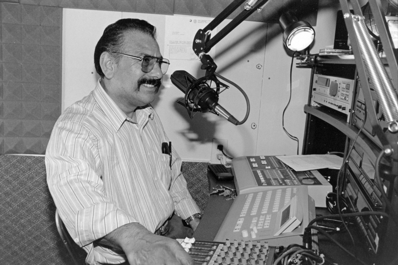 Man speaks into a microphone in a radio studio, equipment in front of him.