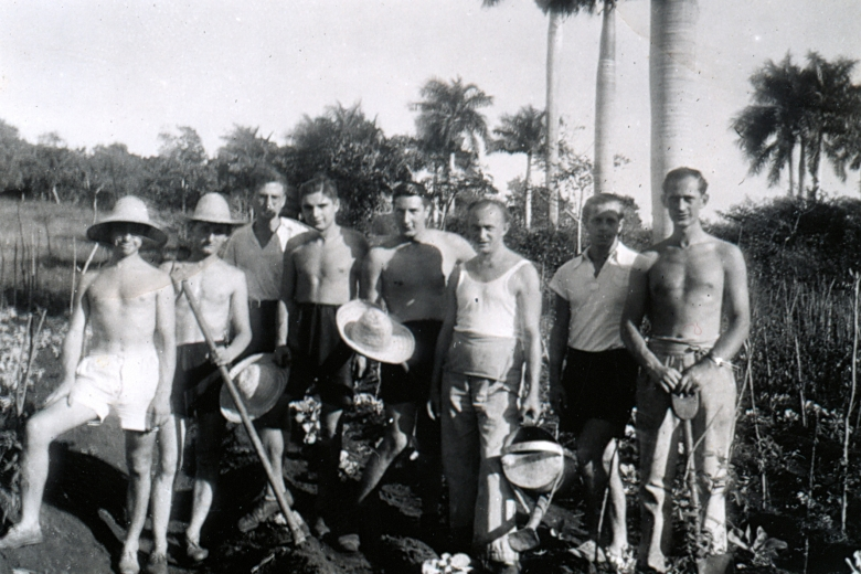Men standing in front of palm trees, some wearing shirts, some without, some wearing wide-brimmed hats.