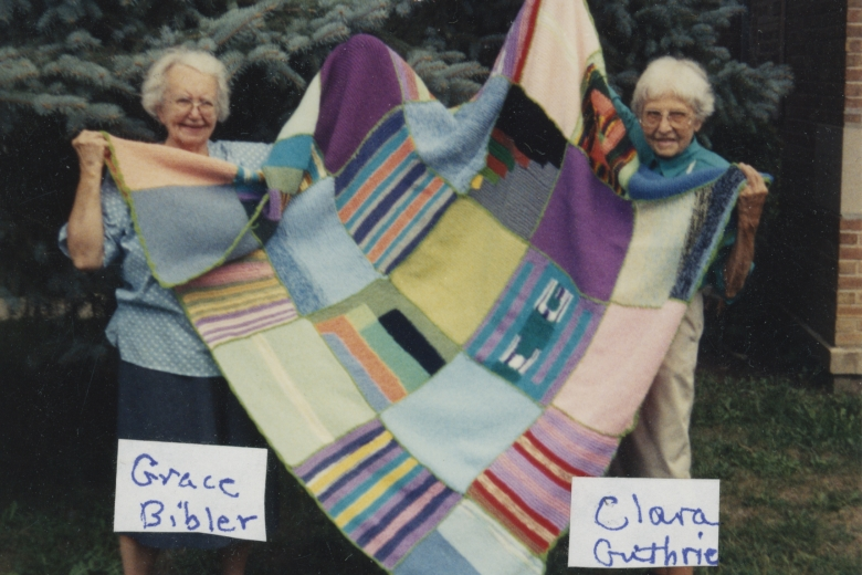 Two elderly women hold up a large blanket.
