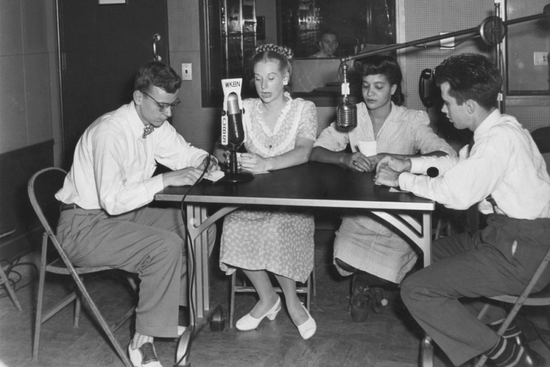 Two men and two women around microphone in radio station.