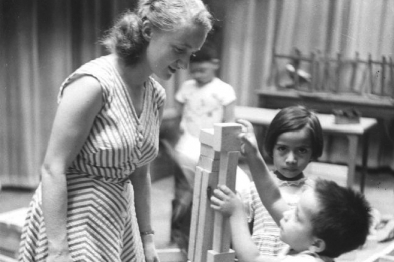 woman helps children build tower with blocks