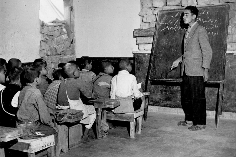 Teacher standing in front of a classroom of students sitting on benches with a blackboard behind him.