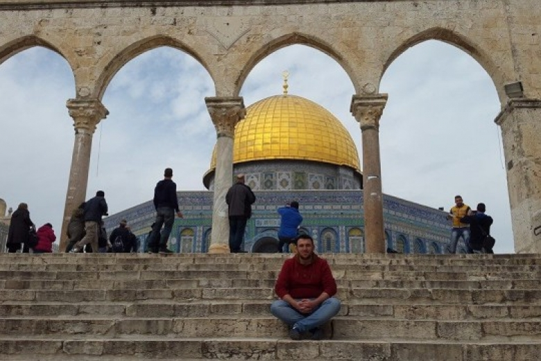 Young man sits cross legged on stairs leading up to a set of archways with the golden dome of a building in the background.