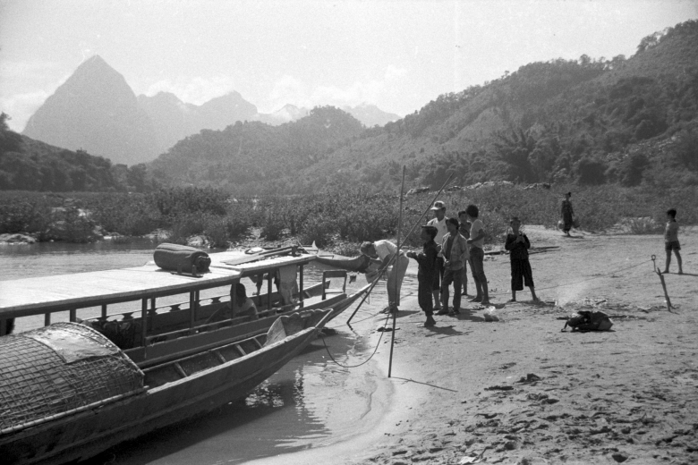 Small group of people stand together on a beach near a boat floating on the nearby body of water.