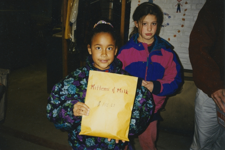 "Two girls stand next to each other, holding an envelope that reads "" Mittens and Milk, $156.63"""