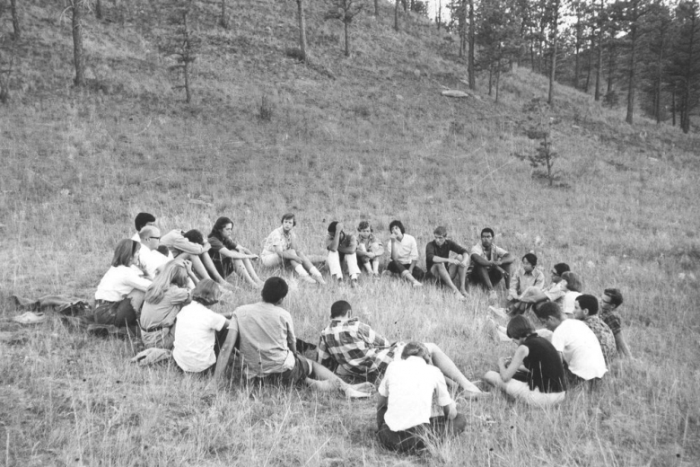 large circle of young men and women in meadow