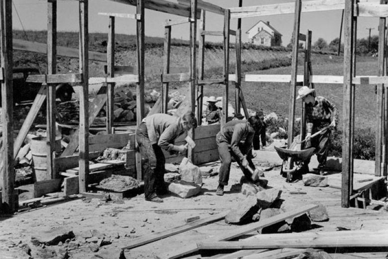 Three people work on the construction of a building
