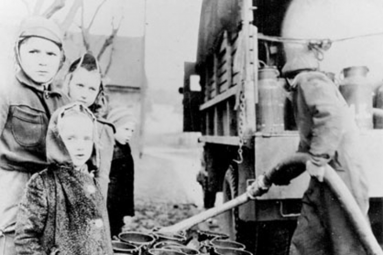 Children stand next to milk jugs being filled by a man using a hose to take milk out of the back of a truck