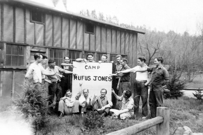 "Group of young men outside a building holding a large sign that reads ""Camp Rufus Jones"""