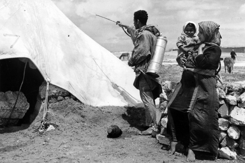 Man wearing a small tank on his back sprays a tent while a woman holding a baby looks on.
