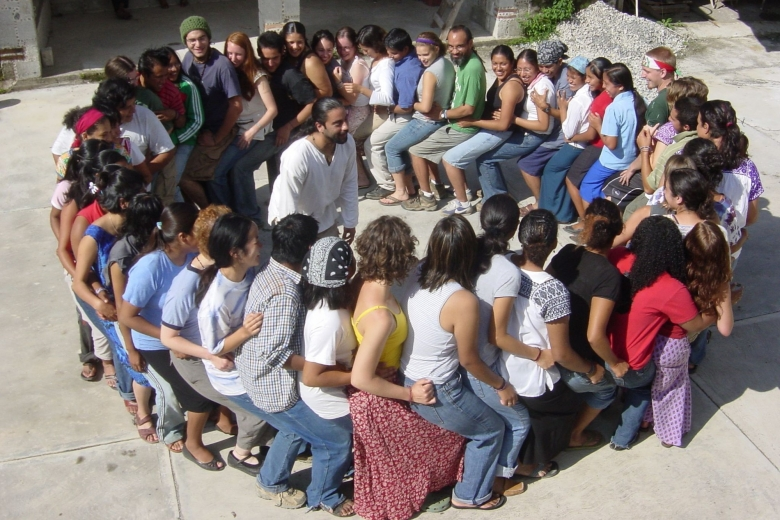 Group of young people form a circle by sitting on one the laps of one another.