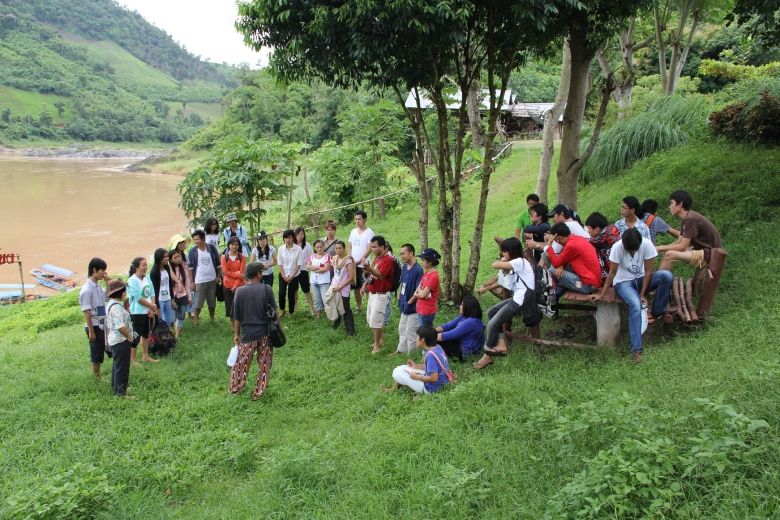 Group of people seated and standing on a grassy hillside next to a river.