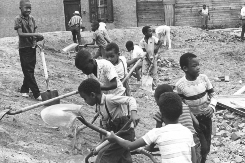 line of small boys digs in vacant lot