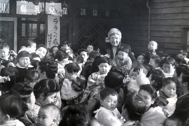 Woman standing in a crowd of women holding babies