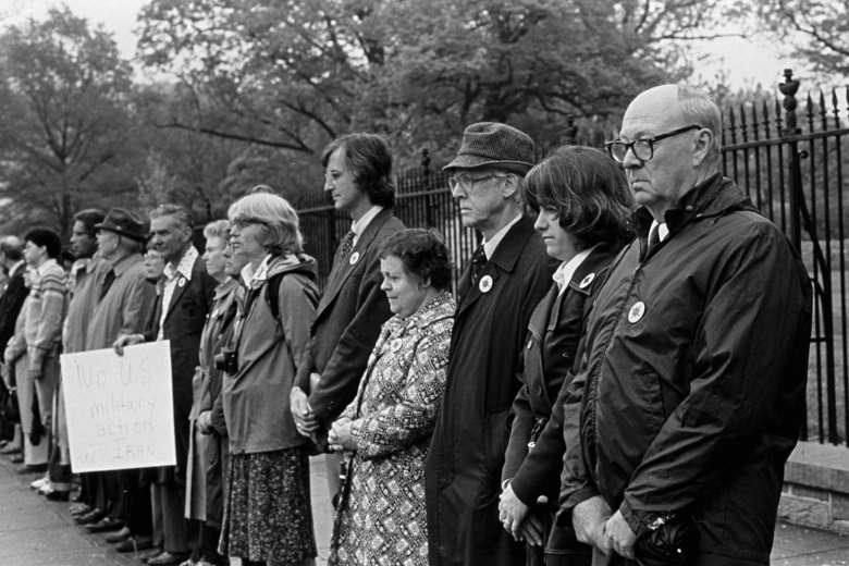 Line of adult men and women with buttons on their jackets standing outside a fence