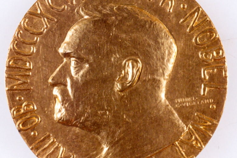 Image of the Nobel Peace Prize metal that is decorated with the profile of a man's head and lettering around the edge.