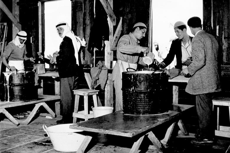 Men work around large kettles.