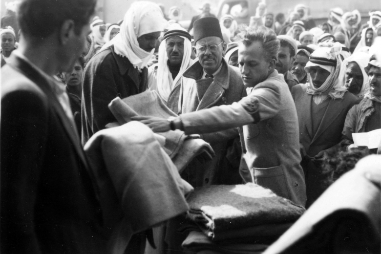 Man with armband hands out blankets to members of a crowd.