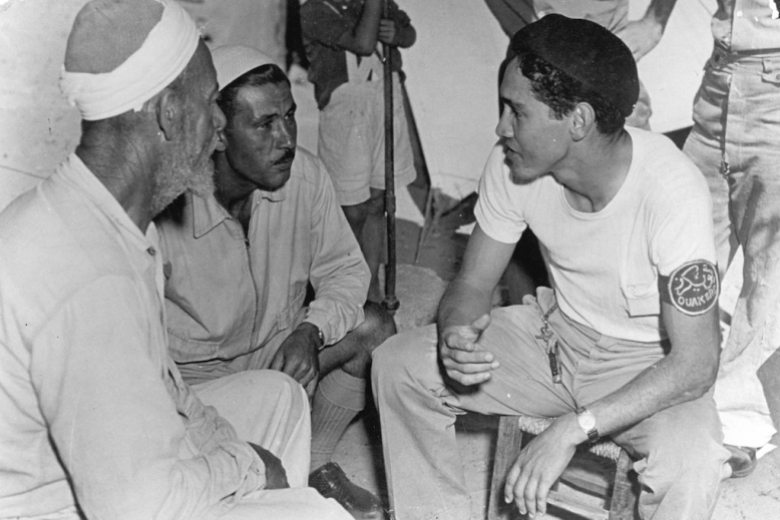 Man wearing a Quaker armband talks with two other men, all seated.