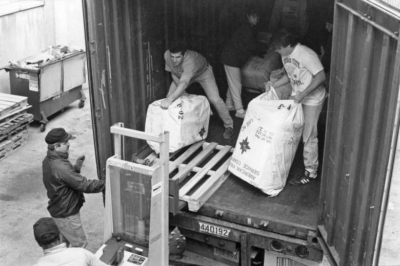 Men unload large sacks of goods onto pallets from a container truck.