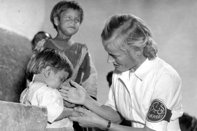 Woman with Quaker armband examines a young child while a slightly older boy looks on.