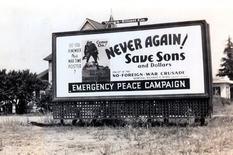"Photograph of a billboard that reads ""Never again! Save sons and dollars."""