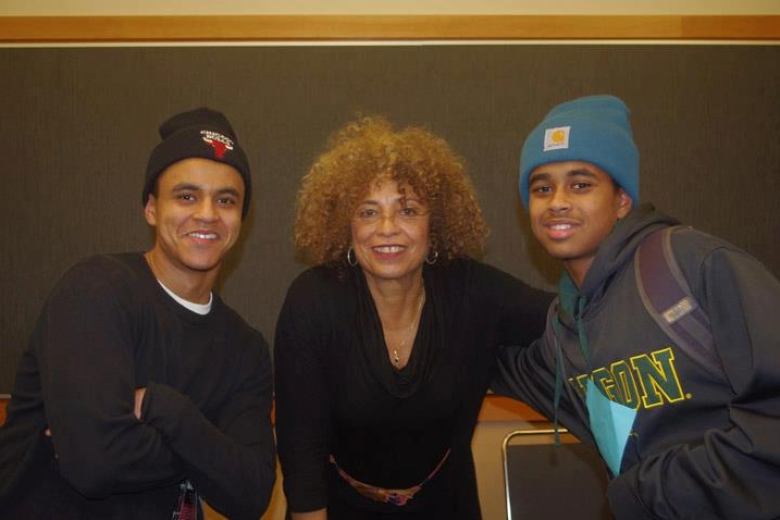 Two young men and a woman pose together for a photo.