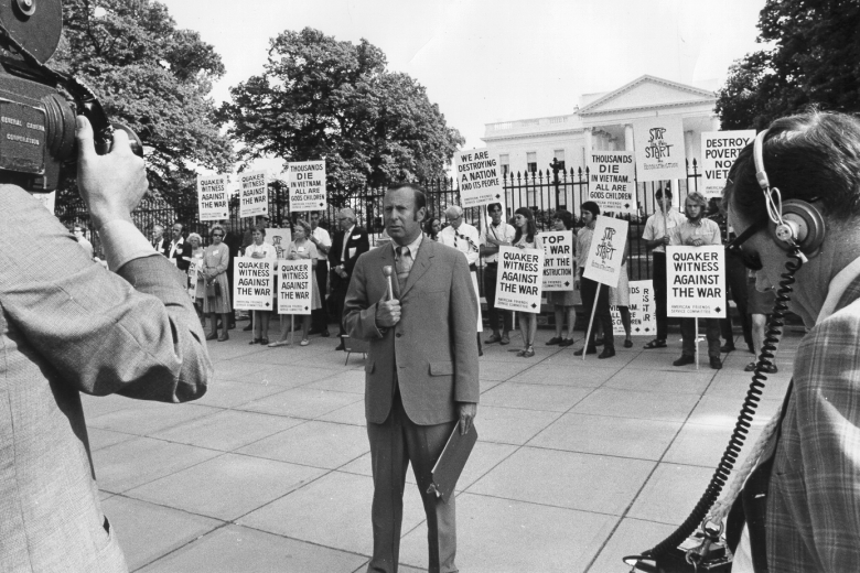 Man with microphone being filmed in front of a group of protesters holding signs with messages against the Vietnam War in front of the White House.