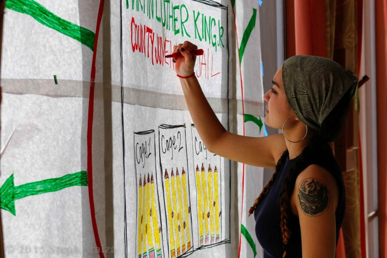 Woman writes on flip chart paper taped to a window.