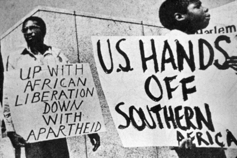 """Two people hold signs that read """"U.S. Hands Off Southern Africa"""" and """"Up with African Liberation Down with Apartheid."""""""